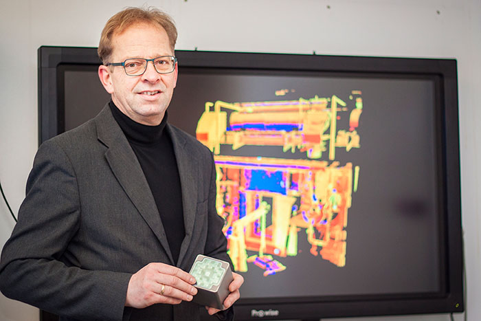 "Stefan Seipel with a ""range camera"" which measures a 3D picture. The image on the screen in the background is a 3D laser scanned part of an industrial facility."